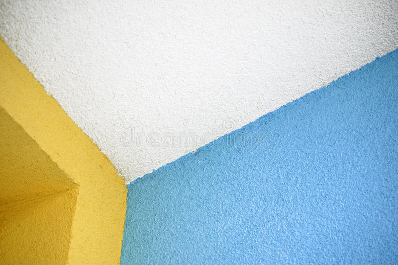 White ceiling edge with colorful blue and yellow walls, coated with roughcast royalty free stock photo
