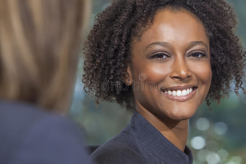 Beautiful Mixed Race African American Woman Businesswoman. A beautiful mixed race African American young woman or businesswoman smiling with perfect teeth stock images