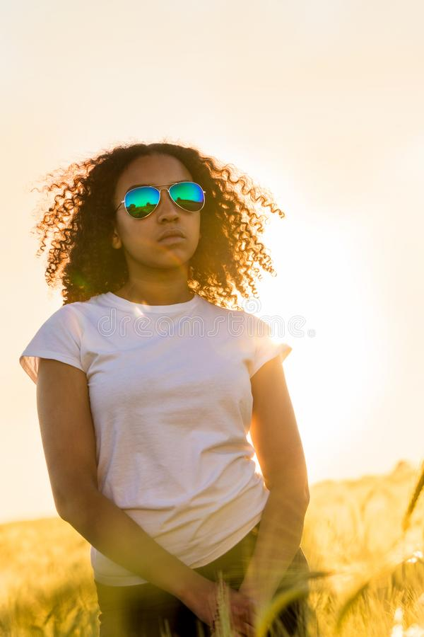 Mixed Race African American Girl Teen Sunglasses Sunset in Field. Beautiful mixed race biracial African American female girl teenager young woman wearing royalty free stock photography