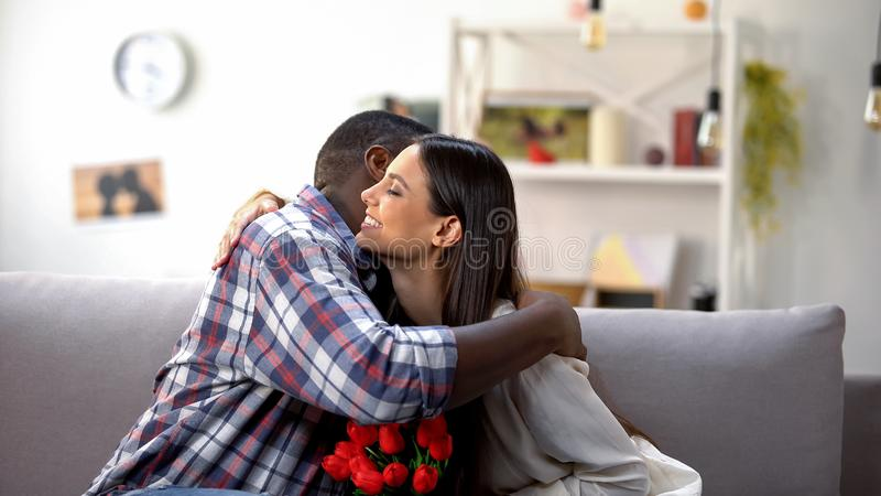Beautiful mixed-race couple hugging with bouquet of tulips, loving relationship royalty free stock photos