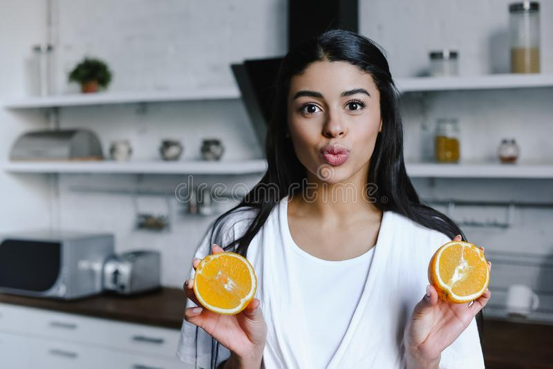 Beautiful mixed race girl in white robe holding cut orange, grimacing and looking at camera in morning. In kitchen royalty free stock photos