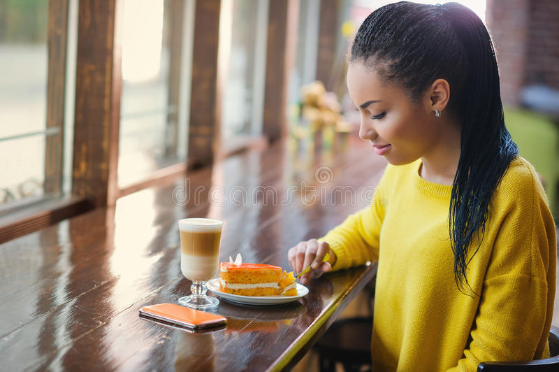 Beautiful mixed race teenage girl in coffee shop stock photography
