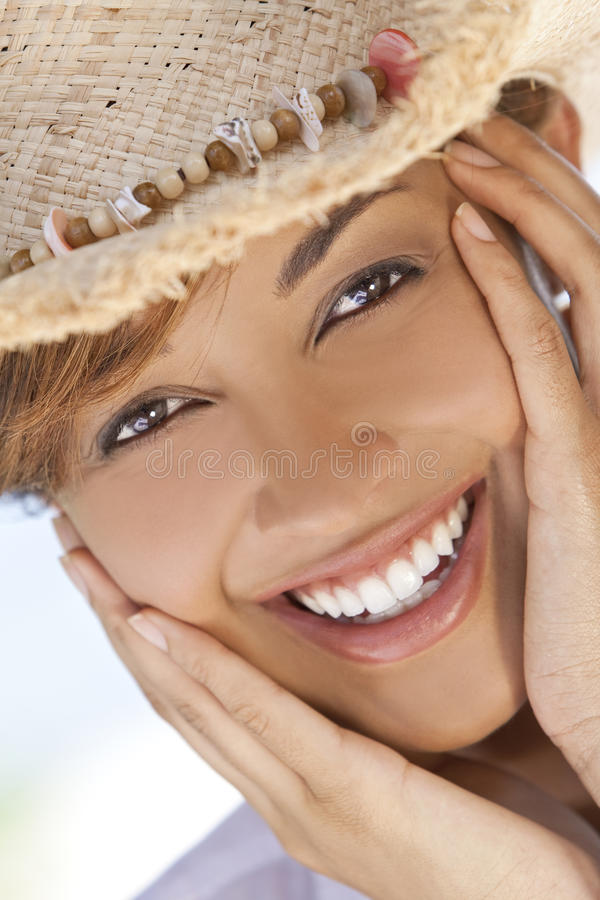Beautiful Mixed Race Woman Laughing In Cowboy Hat. A beautiful mixed race young woman laughing and having fun wearing a straw cowboy hat, shot under a palm tree stock images