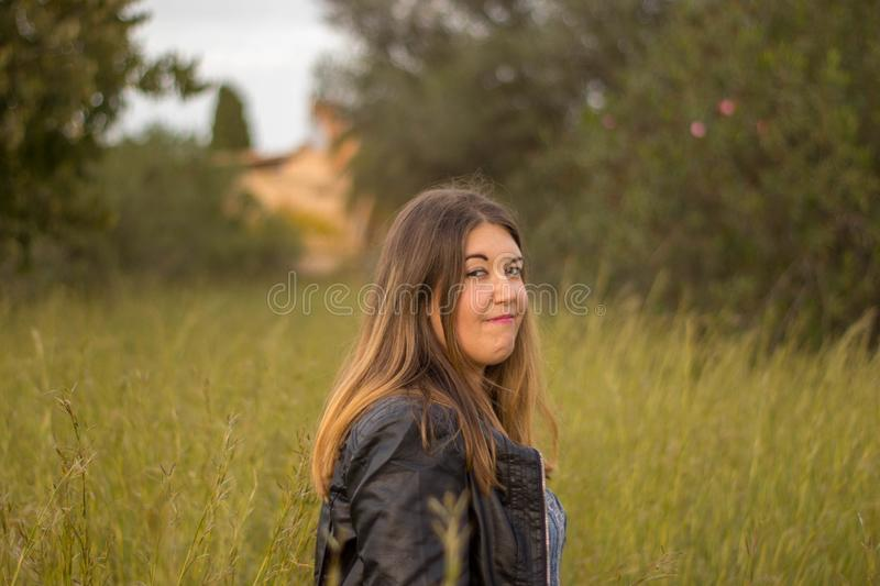 Model with black jacket on outside forest background stock photo