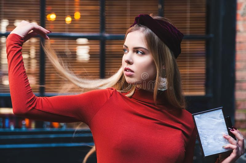 Beautiful model with blond hair poses against the backdrop of large windows and looks away. Skin retouching close-up stock image