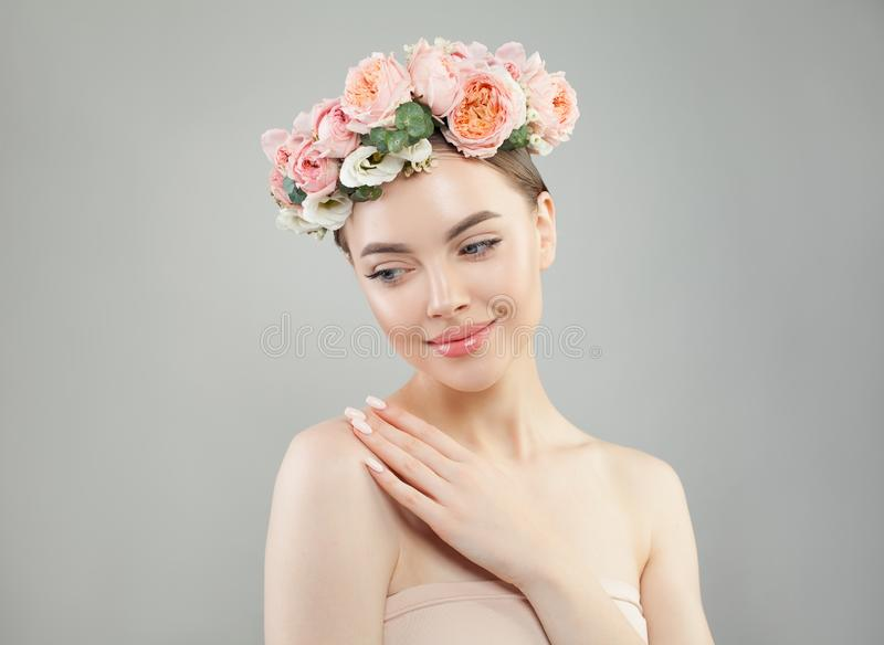 Beautiful model with clear skin and flowers on white background royalty free stock photography
