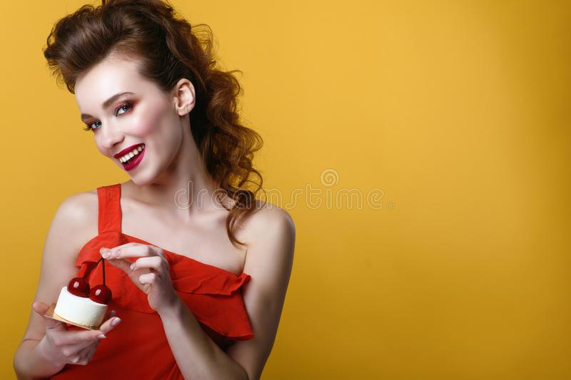 Beautiful model with creative hairstyle and colourful make up holding tasty pastry decorated with cherries on the top stock image