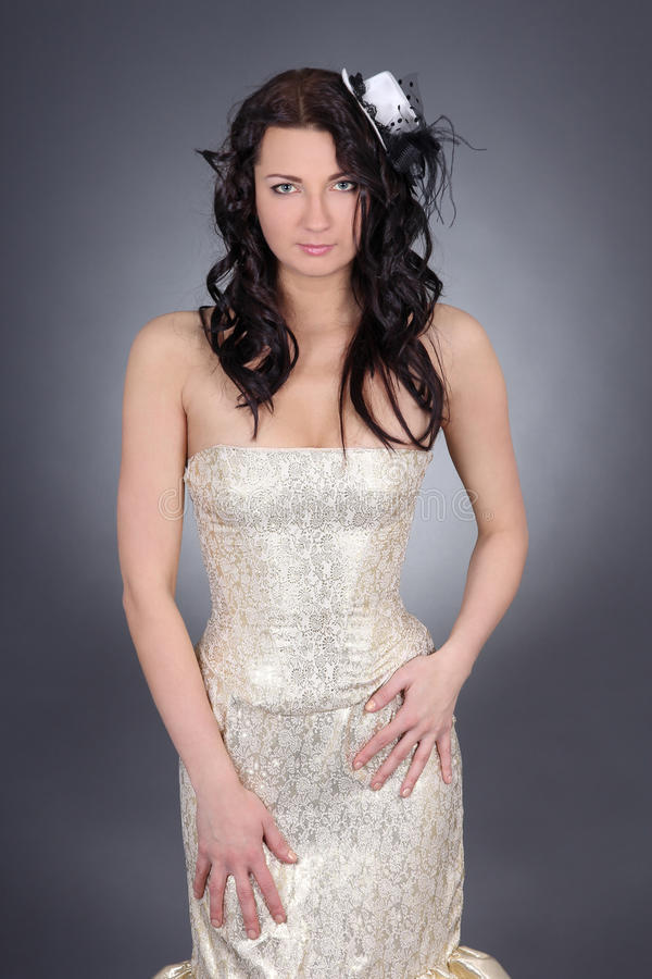 Beautiful Model With Curly Hair In Golden Dress Royalty Free Stock Image