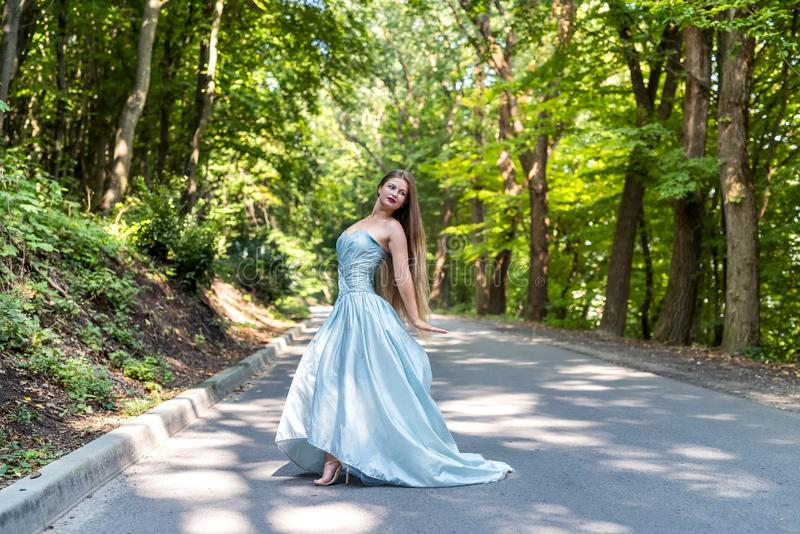 Beautiful model dressed in fashionable dress posing outdoors royalty free stock image