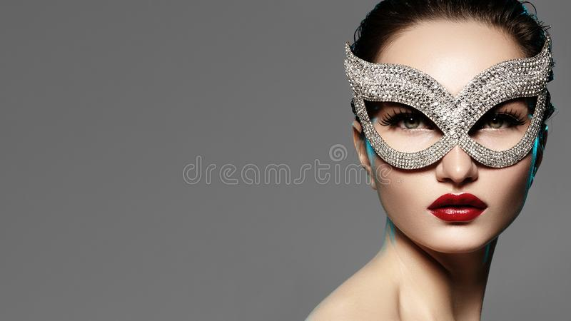 Beautiful Model with Fashion Lips Makeup Wearing Bright Brilliant Mask. Masquerade Style Woman. Holiday Celebration Look. Horizontal Beauty Photo royalty free stock photos
