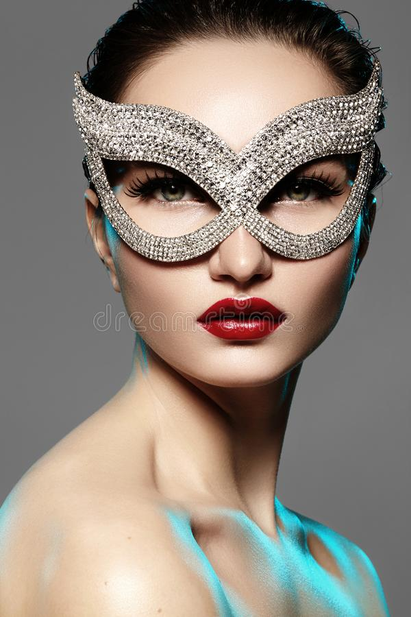 Beautiful Model with Fashion Lips Makeup wearing bright brilliant mask. Masquerade style woman. Holiday celebration look stock photo
