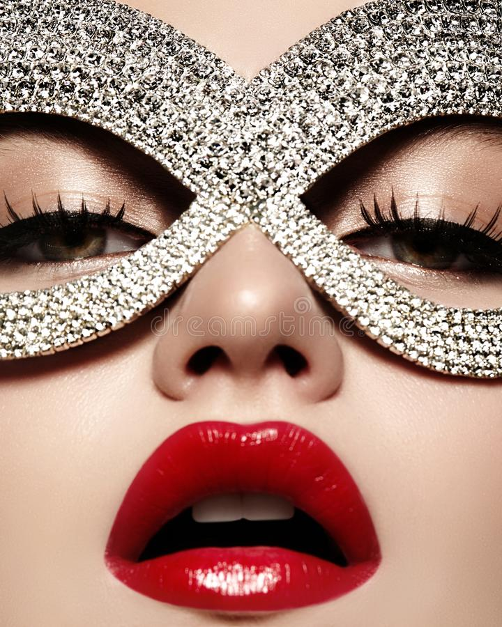 Beautiful Model with Fashion Lips Makeup wearing bright brilliant mask. Masquerade style woman. Holiday celebration look. Beautiful Model with Fashion luxe Lips stock photography