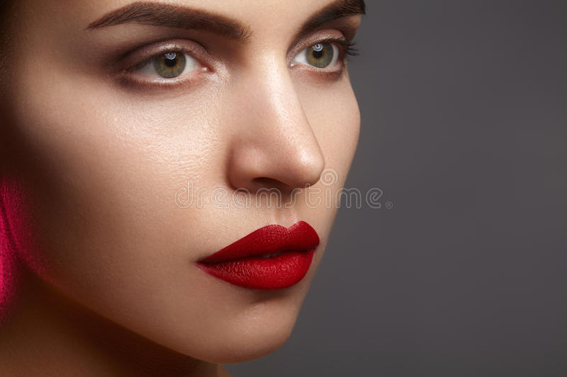Beautiful model with fashion make-up. Close-up portrait woman with glamour lip gloss makeup and bright eye shadows. Macro shot of celebrate visage, clean skin royalty free stock photos
