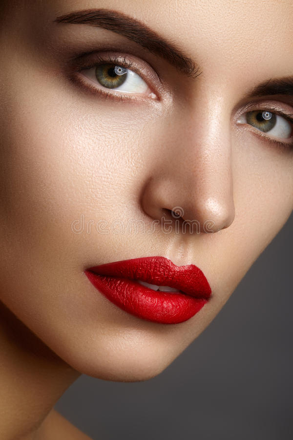 Beautiful model with fashion make-up. Close-up portrait woman with glamour lip gloss makeup and bright eye shadows. stock photos