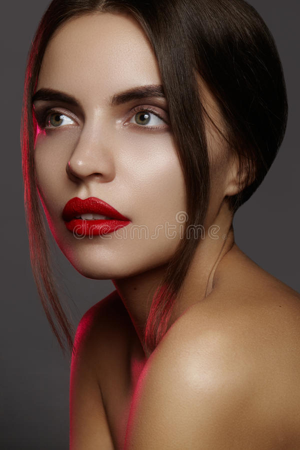 Beautiful model with fashion make-up. Close-up portrait woman with glamour lip gloss makeup and bright eye shadows. stock photography