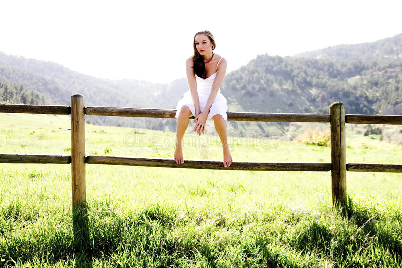 Beautiful Model on a fence. A model looking at the camera while sitting on a fence royalty free stock photos