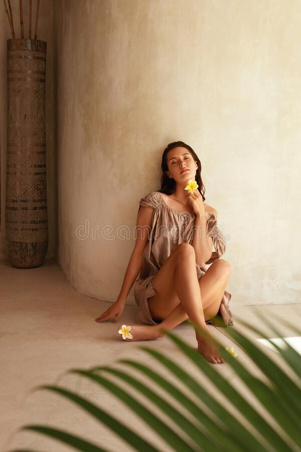 Beautiful Model With Flowers. Portrait Of Seductive Tanned Woman With Perfect Body And Smooth Skin Behind Palm Leaf. royalty free stock photo