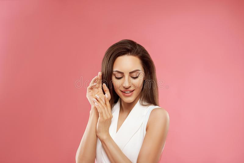 Beautiful model girl with a beige French manicure nail . Fashion makeup and care for hands and nails and cosmetics. stock photo
