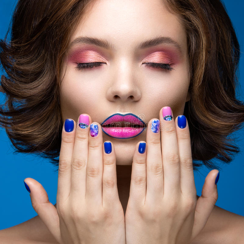 Beautiful model girl with bright makeup and colored nail polish. Beauty face. Short colorful nails. Picture taken in the studio on a blue background royalty free stock images