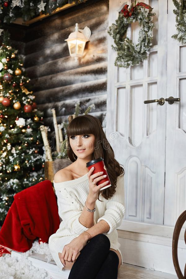 Beautiful model girl in a knitted sweater and long socks with a cup of coffee posing near Christmas tree. Young woman in stock photography