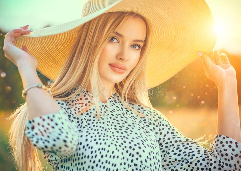 Beautiful model girl posing on a field, enjoying nature outdoors in wide brimmed straw hat. Beauty blonde young woman royalty free stock photos