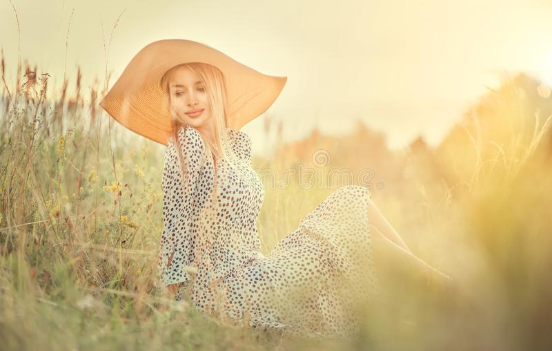 Beautiful model girl posing on a field, enjoying nature outdoors in wide brimmed straw hat. Beauty blonde young woman with long straight blond hair close-up royalty free stock images