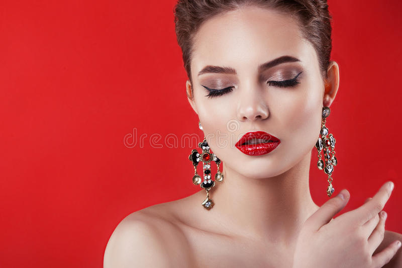Beautiful model girl on a red background . The beauty of a woman royalty free stock image