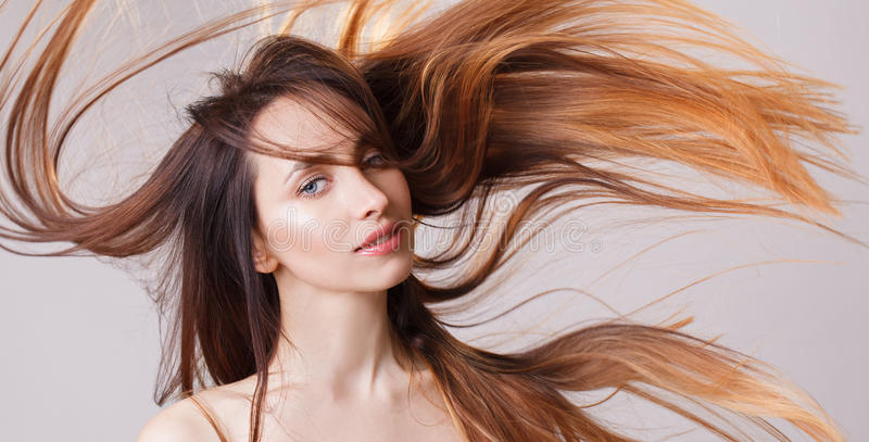Beautiful model girl with shiny flying brown ombre straight long hair . Care and hair products . Grey background royalty free stock photo