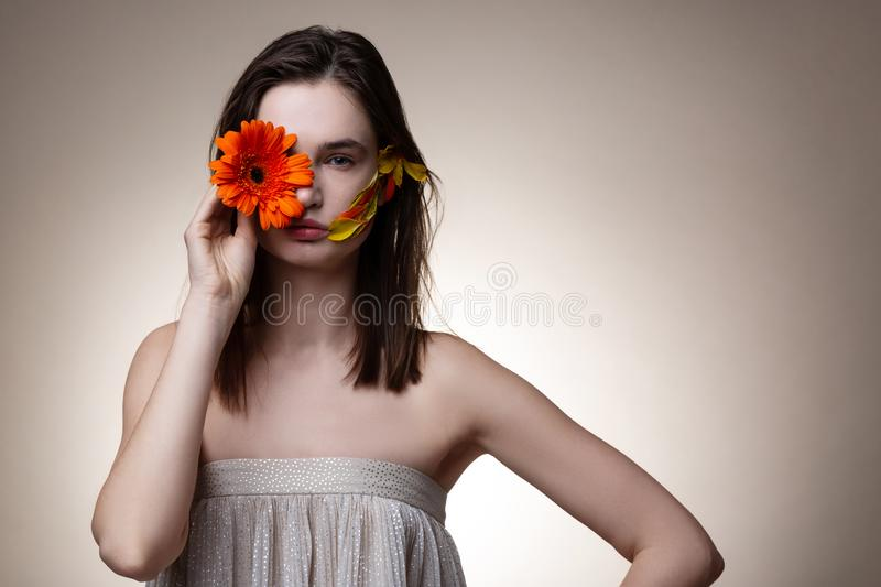 Beautiful model hiding half of her face with orange flower royalty free stock image