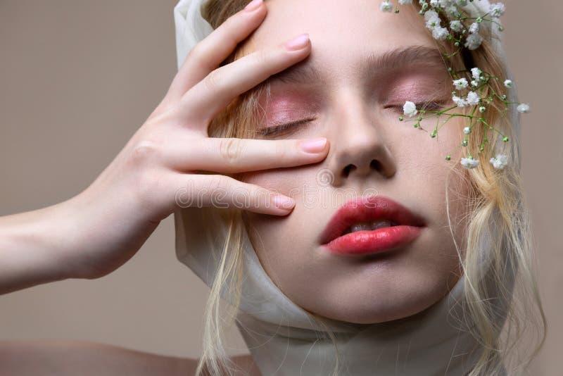 Beautiful model with light pink eyeshades closing eyes while posing stock photo