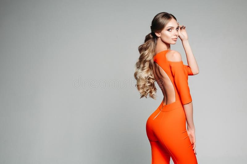 Beautiful model with long wavy hair in tail wearing orange overall with open back. royalty free stock photo