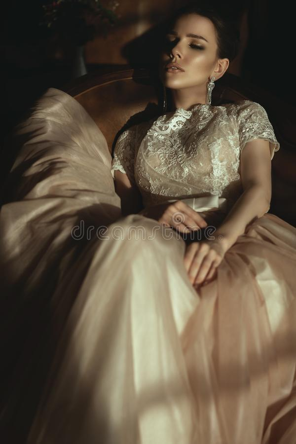 Beautiful model in luxurious puffy dress with veiling skirt sitting relaxed in the armchair royalty free stock photo