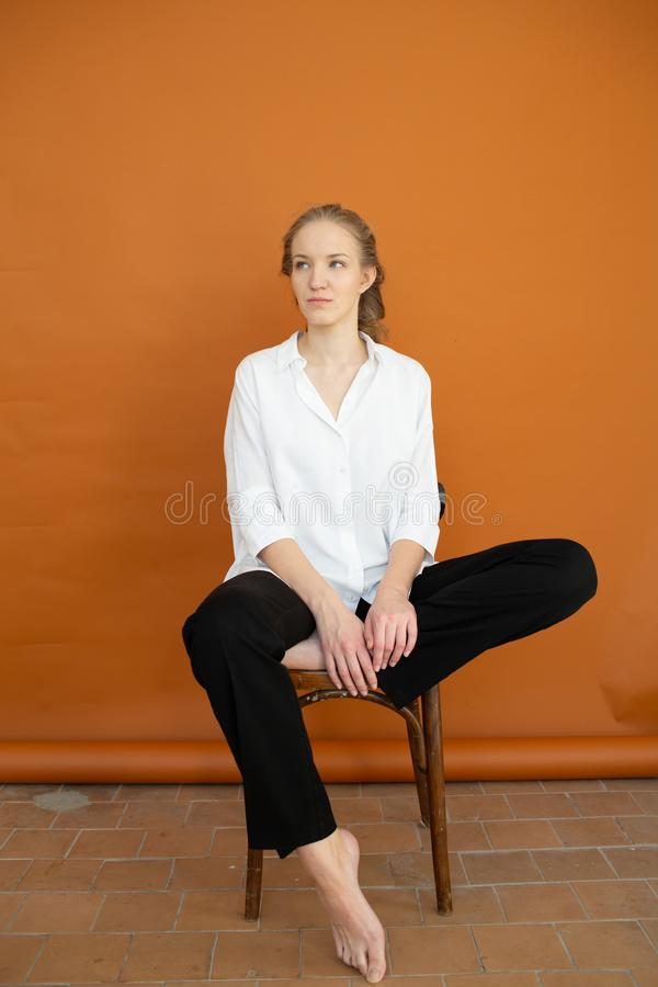 Beautiful model on orange background sitting on the chair in white shirt and black trousers royalty free stock image