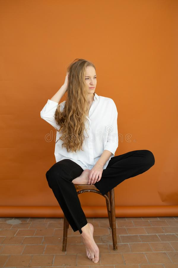Beautiful model on orange background sitting on the chair in white shirt and black trousers stock images