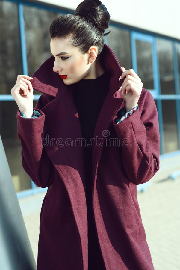 Beautiful model with perfect make up and hair scrapped back into a bun holding the popped up collar of her maroon coat stock photography