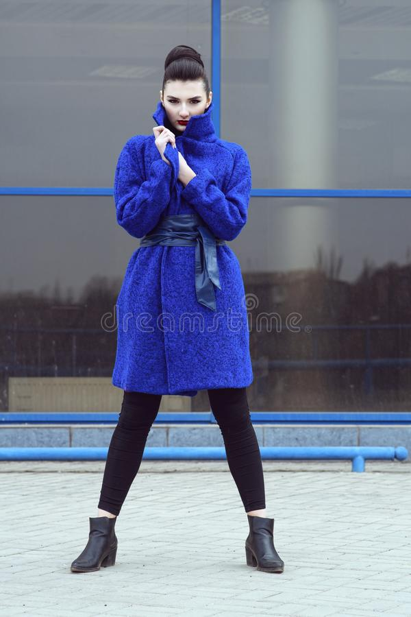 Beautiful model with perfect make up and hair scrapped back into a bun standing on the street in trendy blue coat royalty free stock photos