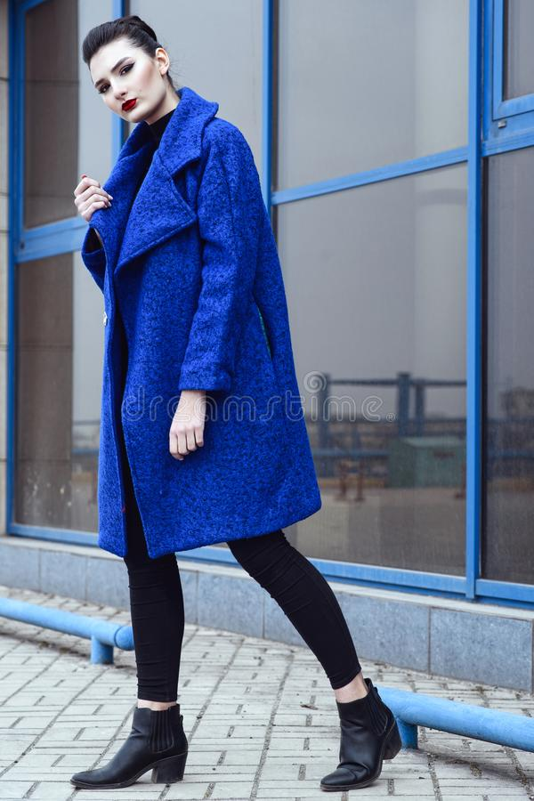 Beautiful model with perfect make up and hair scrapped back into a bun walking in trendy blue coat stock images