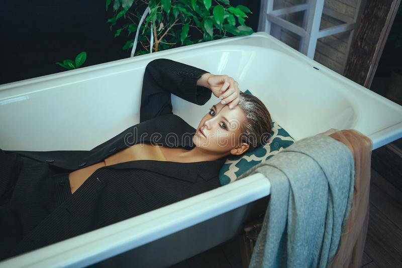 Beautiful model is posing in a bathroom with creative silver makeup royalty free stock photo