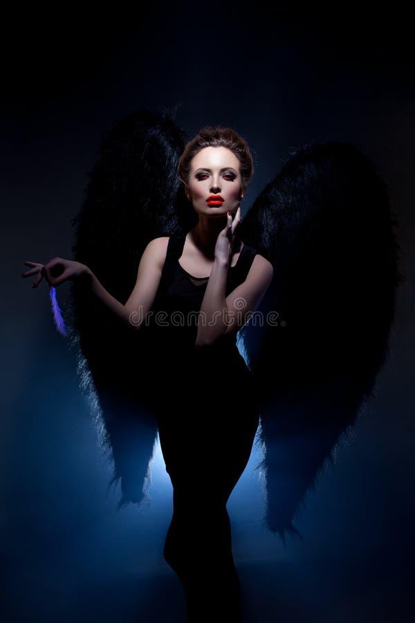 Beautiful model posing in suit of fallen angel