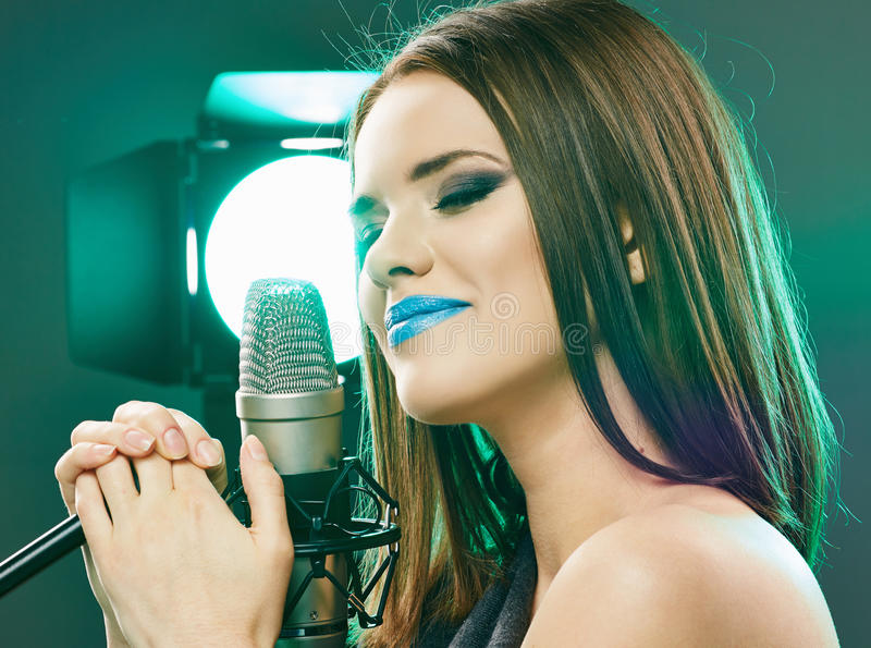 Beautiful Model Sensual singing into a microphone. royalty free stock image