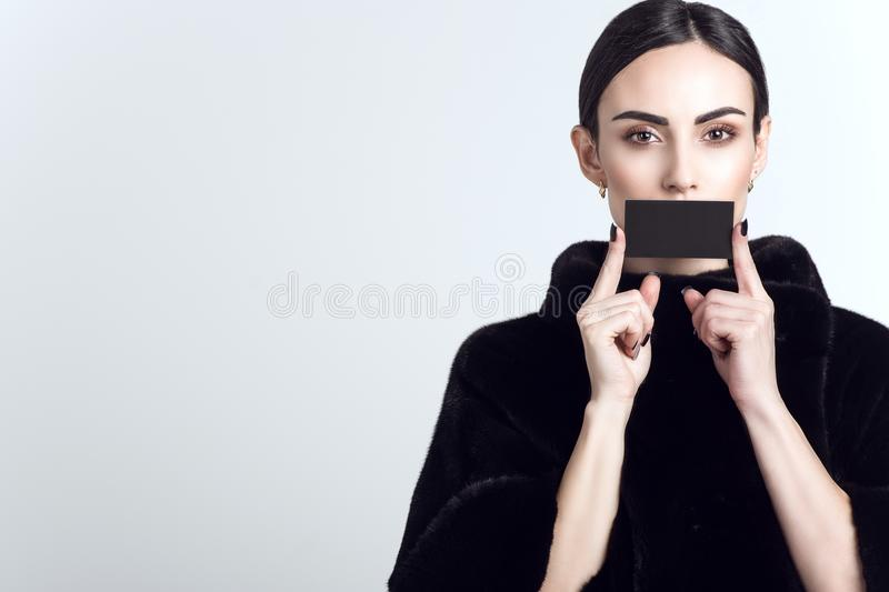 Beautiful model with sleek low ponytail wearing dark mink fur coat and holding black blank visit card in front of her mouth royalty free stock images
