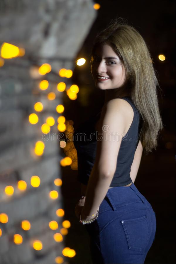 Beautiful model smiling at night together with the colorful lights. a beautiful young lady posing with big smiles on bokeh backgro. Portrait of beautiful young stock photo