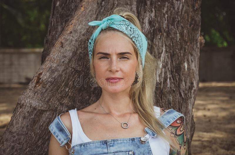 Beautiful model with tattoos sitting on the beach near a tree. Wears a turquoise bandana. A modern woman. Rest in. Paradise stock photos