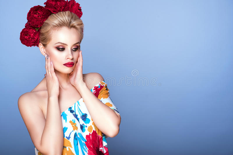 Beautiful model with updo hair and perfect bright make up wearing floral open shoulder dress and fluffy peony head garland stock image