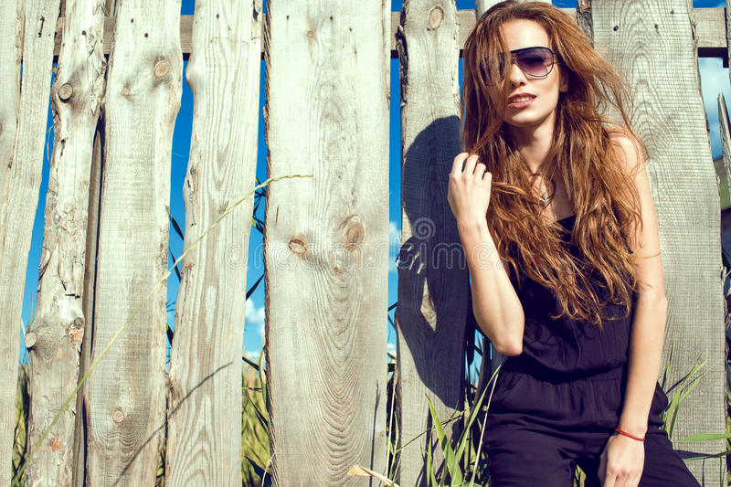 Beautiful model wearing black jumpsuit and trendy aviator sunglasses standing at the old shabby fence made of boards. Young beautiful model with long chestnut stock photos