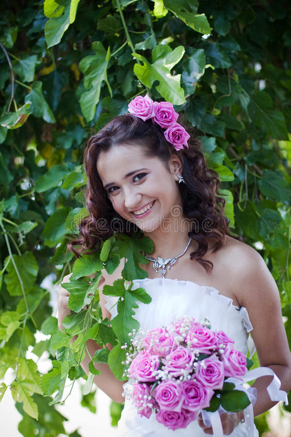 Beautiful model on wedding. Beautiful happy girl on wedding. Wedding photo. Beautiful model on wedding. Model in white dress. Pink roses in hair. Gypsy model on stock photos