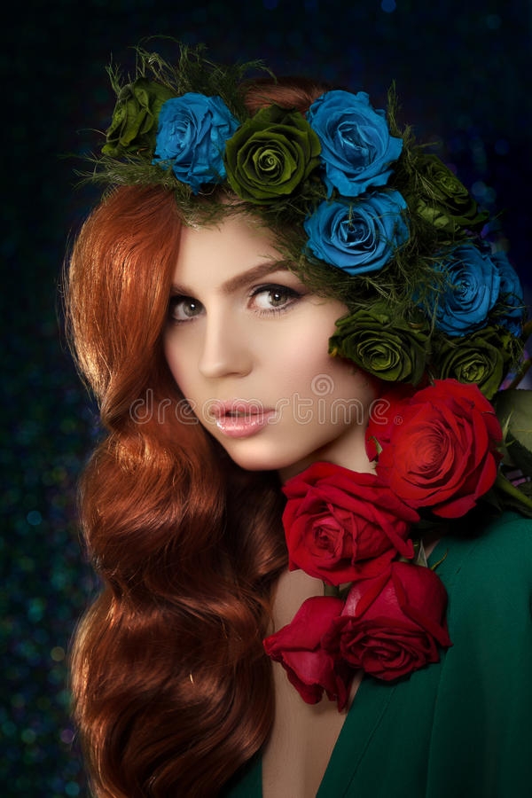 Beautiful model woman with blue, green and redrose flower in hair, beauty salon makeup. Young girl from a fairy tale royalty free stock photo