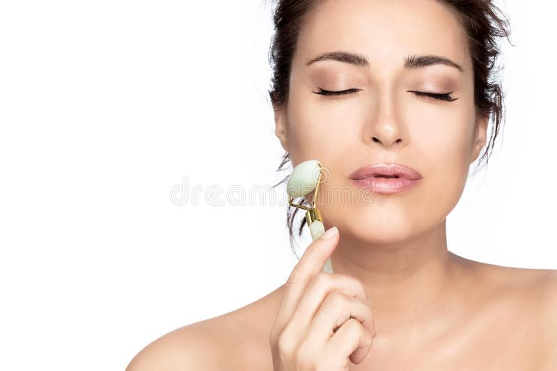 Beautiful model woman with healthy fresh clean skin using a jade roller stock photo