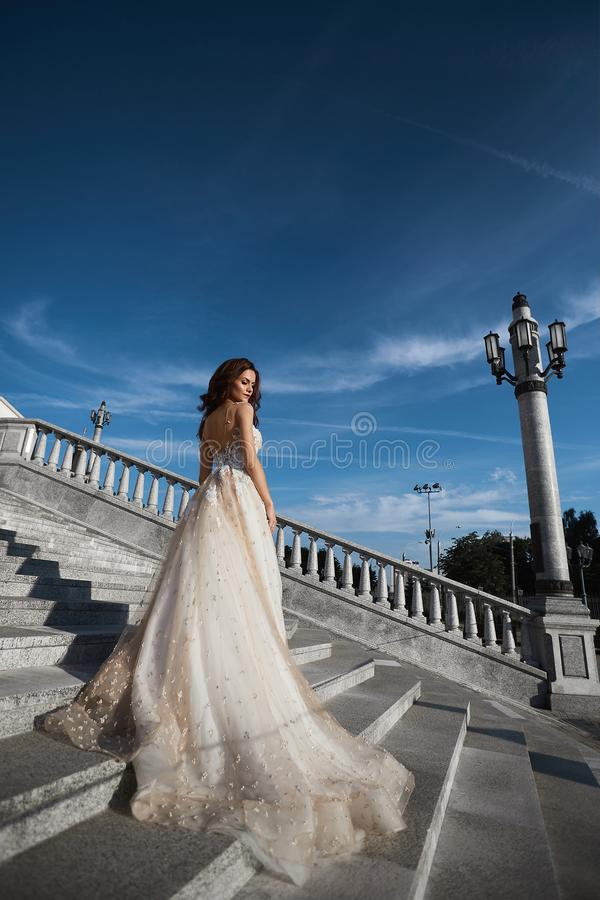 Beautiful model woman with perfect body in luxury wedding dress stands with back on the stairs and posing with blue sky. At background royalty free stock photography