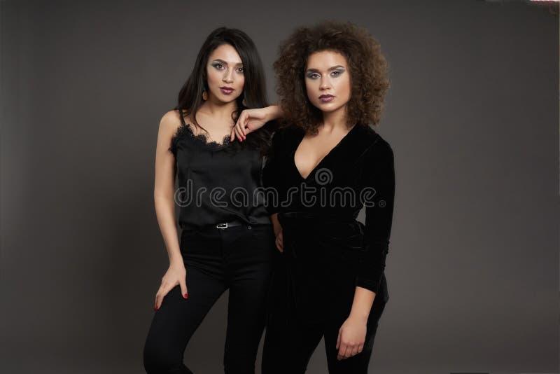Beautiful models in elegant black blouses, trousers. royalty free stock photos